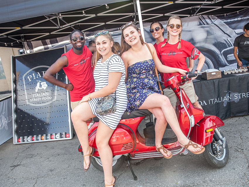Columbus experiential marketing firm employees on red Vespa